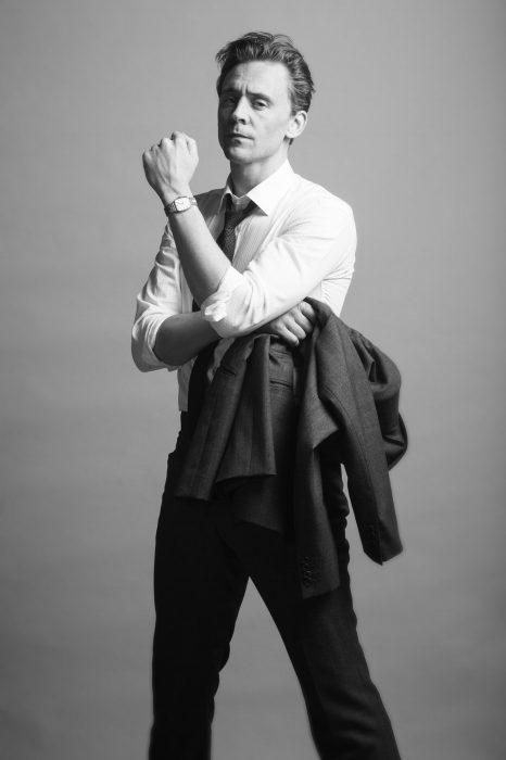 Chico de cabello corto con traje de gala posando para la foto y enseñando su reloj