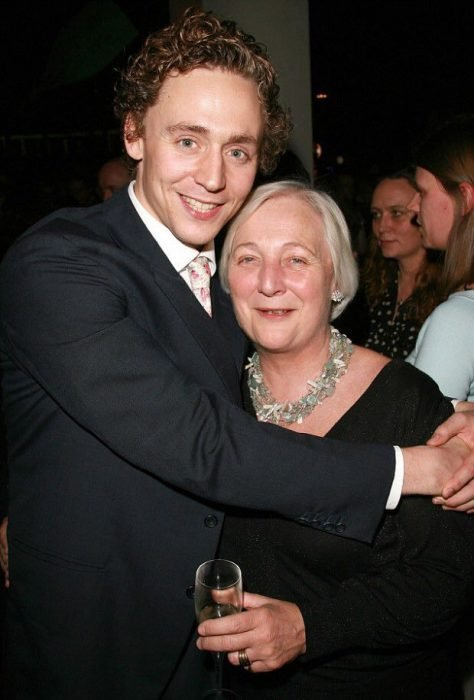 Chico delgado de cabello rubio y chino y ojoz azules vistiendo traje de gala y abrazando a una señora mayor de cabello blanco