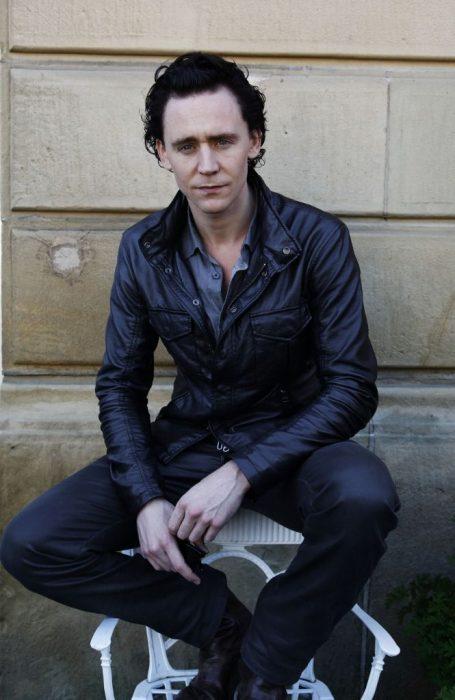 Chido delgado de cabello negro y ondulado de ojos azules y chamarra de piel sentado en una silla blanca
