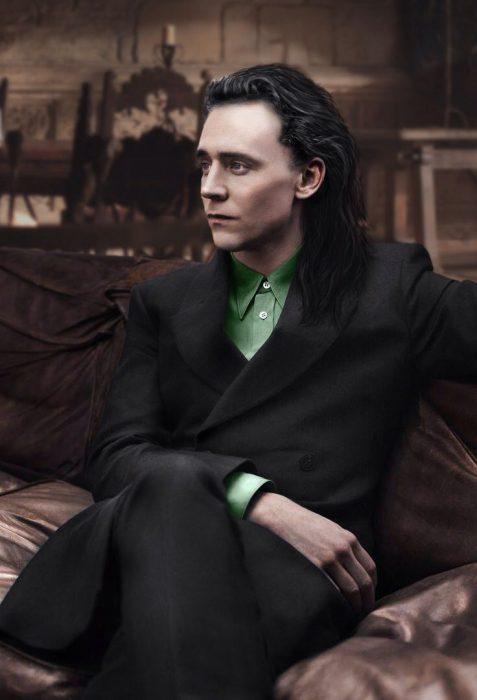 Chido de cabello negro largo vestido de traje con una camisa verde sentado en un asillón