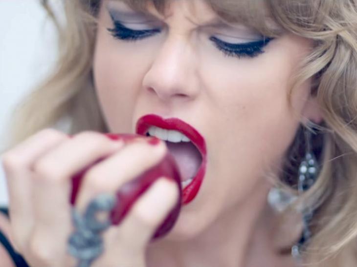 Taylor Swift comiendo manzana, chica rubia mordiendo una manzana roja
