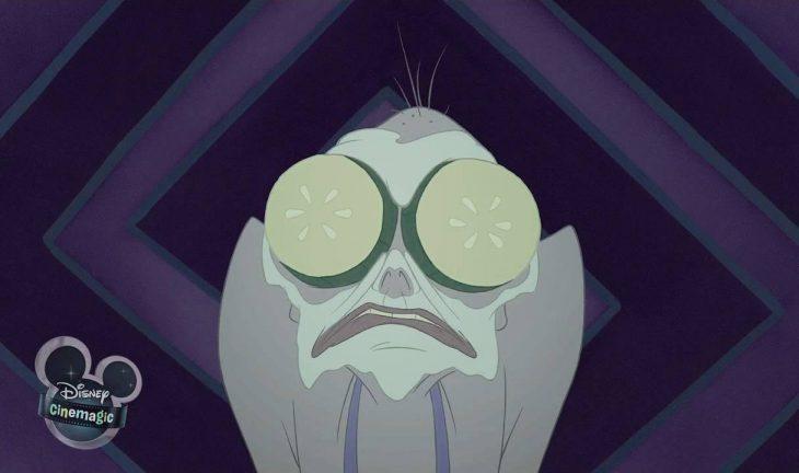 Yzma con una mascarilla y rodajas de pepino en los ojos