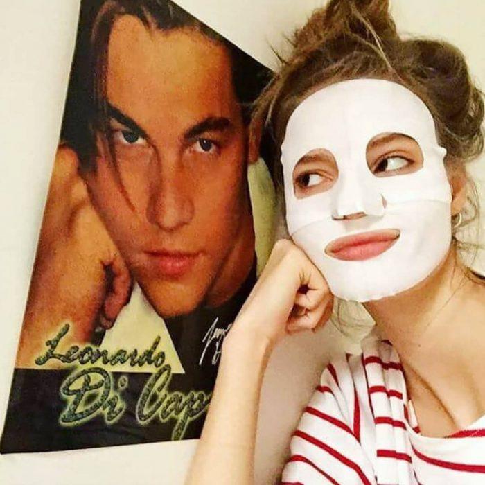Chica utilizando una mascarilla al lado de un poster de Leonardo DiCaprio