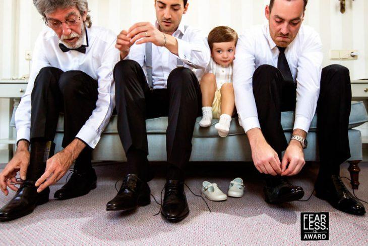 hombres padrinos y un niño pequeño entre ellos