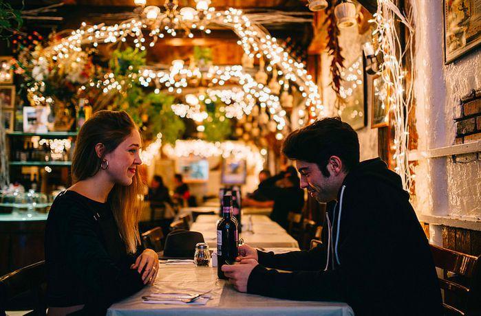 pareja de novios cenando carne y vino