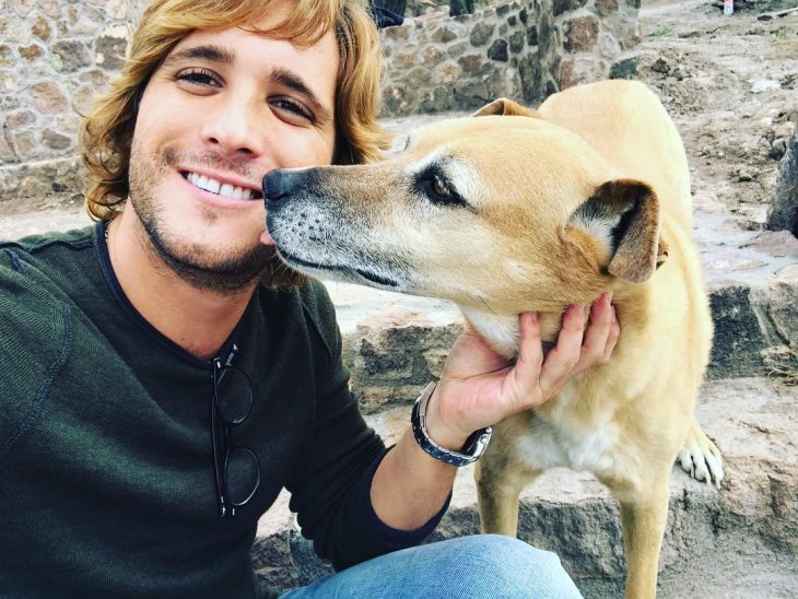hombre rubio sonriendo junto a perro