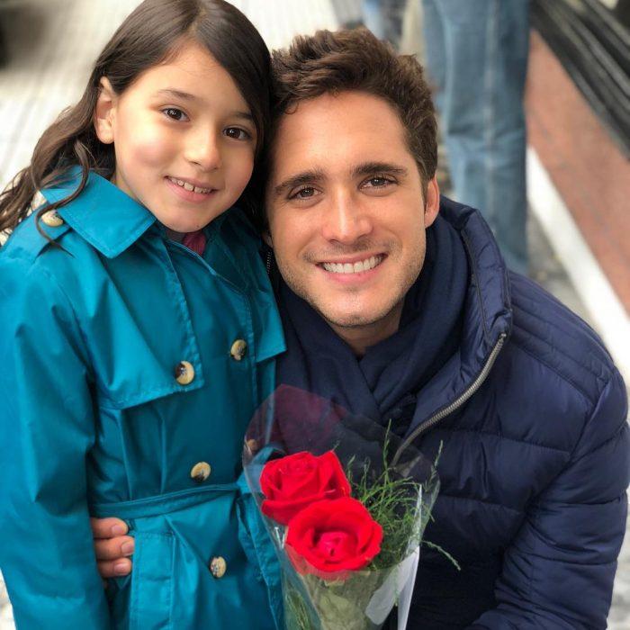 niña junto a hombre y flores rojas