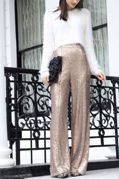 mujer con pantalón de brillos y blusa apeluchada