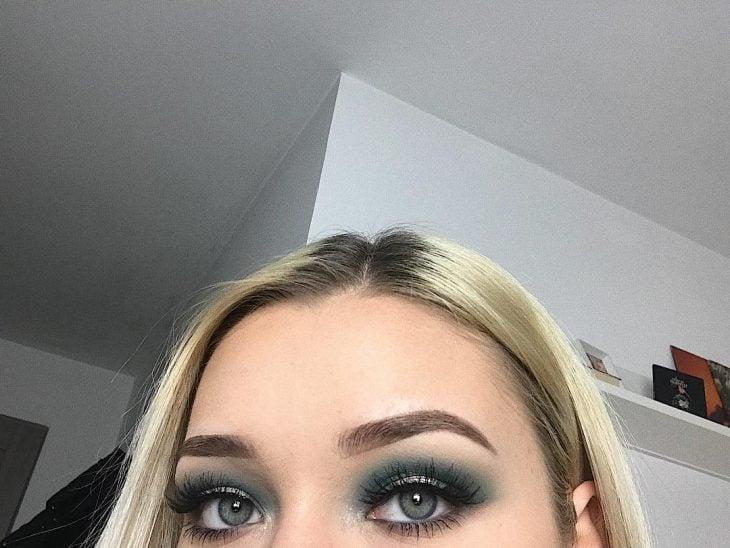 ojo de mujer blanca con cabello rubio y sombra verde