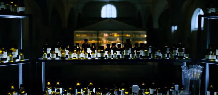 estante con frascos de perfumes en oscuridad