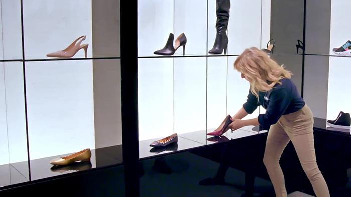 Mujer rubia en zapatería viendo una zapatilla