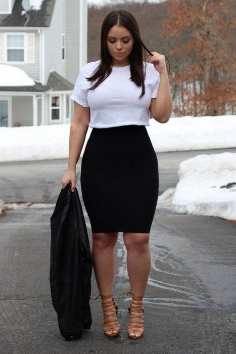mujer con falda negra y camisa corta blanca