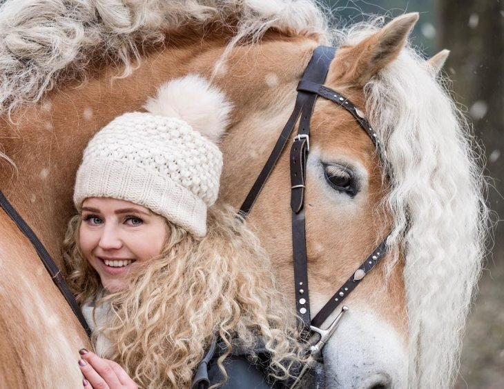 mujer rubia con cabello rizado arriba de un caballo