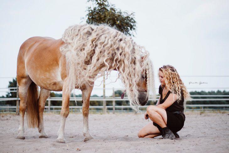 mujer rubia con cabello rizado y caballo