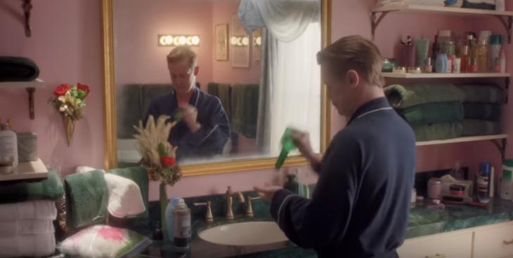 hombre rubio frente espejo en baño