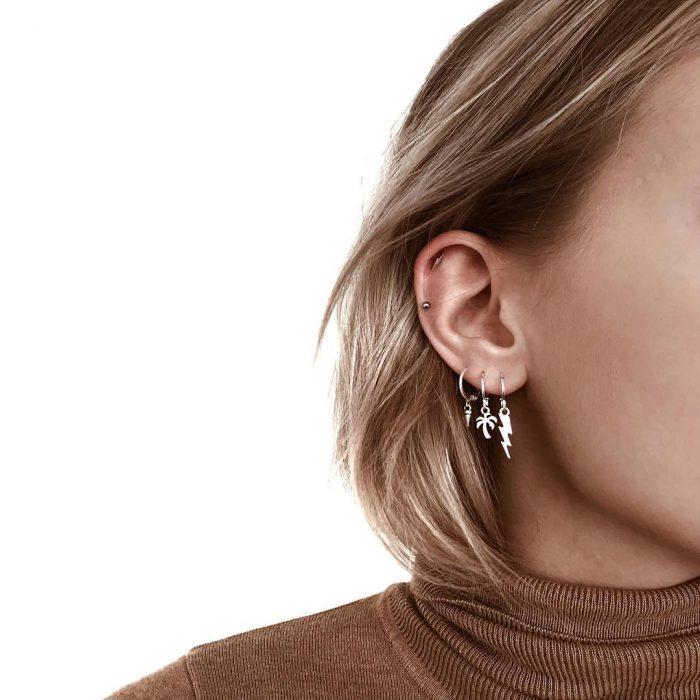 oreja de mujer con pearcings y aretes