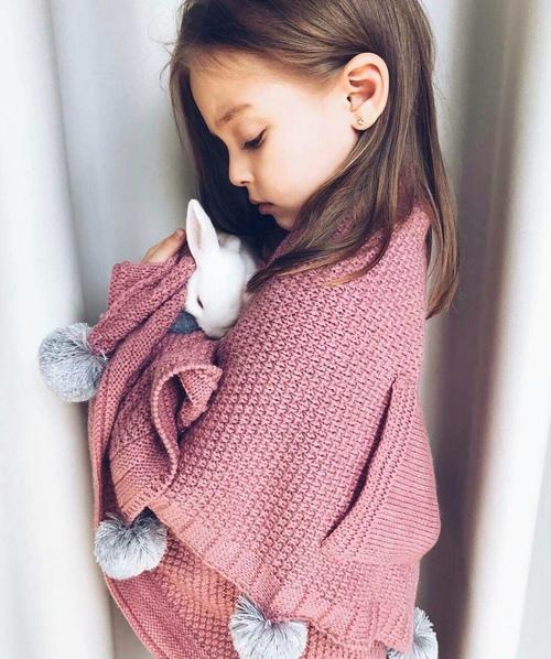 niña con conejo y sueter rosa