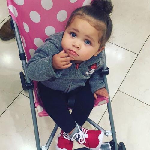 niña con ojos azules sentada en carreola