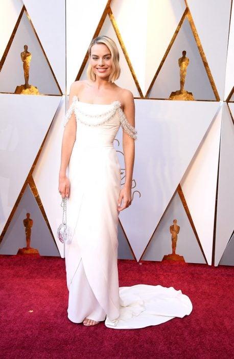 mujer rubia con cabello corto y vestido blanco