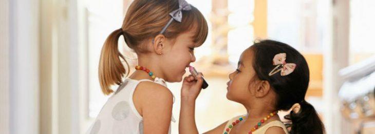 dos niñas con diademas pintándose la boca