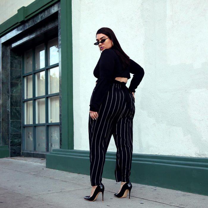 mujer con pantaón negro de rayas y tacones