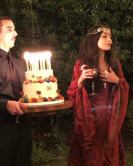 mujer con vestido rojo cabello largo y pastel con velas