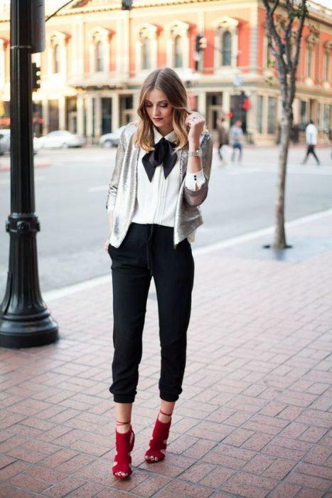 mujer con pantalón negro y camisa blanca con moño