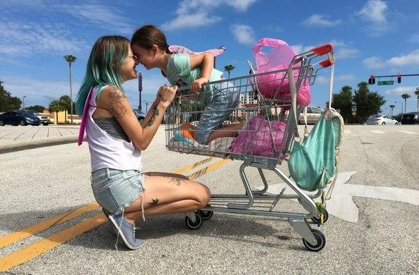 madre e hija jugando con carrito de supermercado