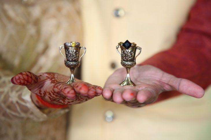 manos de hombre y mujer con trofeo pequeño