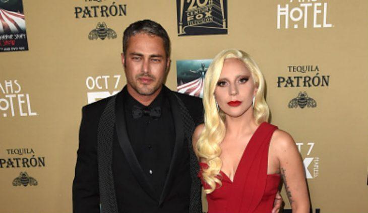 hombre con traje negro y mujer con vestido rojo
