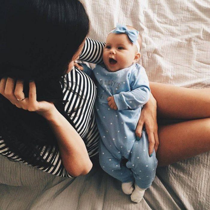 mujer con bebè con mameluco azul en sus brazos