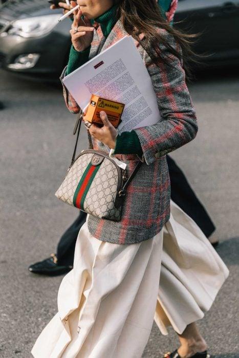mujer con saco de cuadros y bolso y logo enfrente