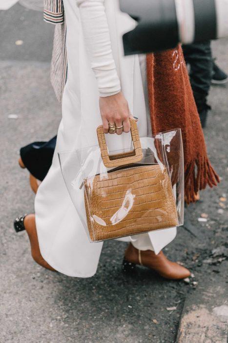 mujer con traje blanco y zapatos y bolsa de plástico y bufanda