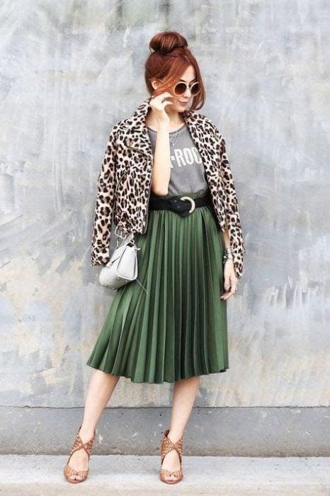 mujer falda verde plizada y chamarra leopardo