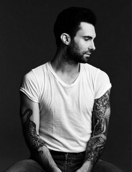 Adam Levine de Maroon 5, hombre con tatuajes y playera blanca