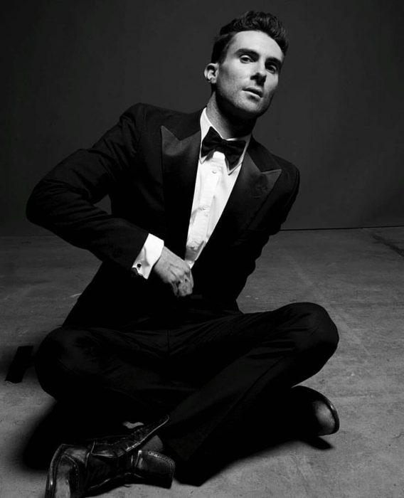 Adam Levine de Maroon 5, hombre con traje negro y corbata de moño