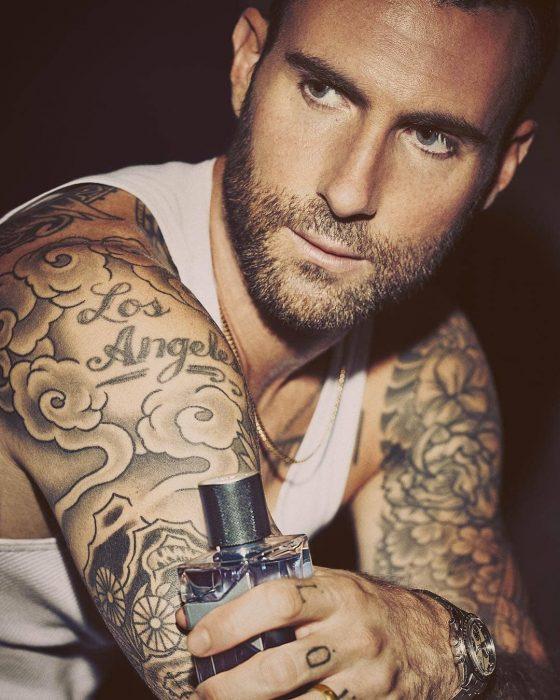Adam Levine de Maroon 5, hombre con tatuajes, barba y playera blanca con perfume