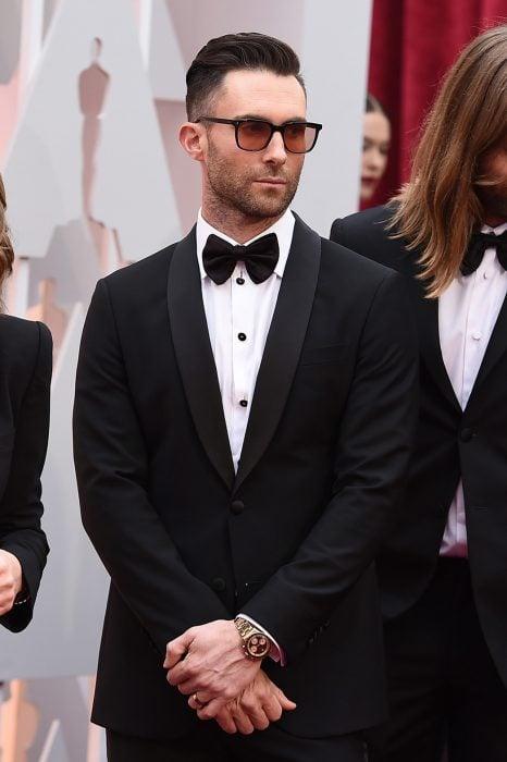 Adam Levine de Maroon 5, hombre con barba, traje negro usando lentes para sol