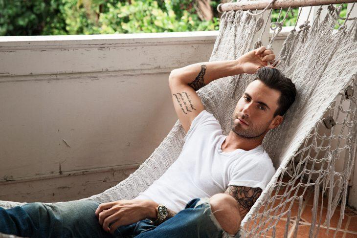 Adam Levine de Maroon 5, hombre con tatuajesm barba y playera blanca en una hamaca