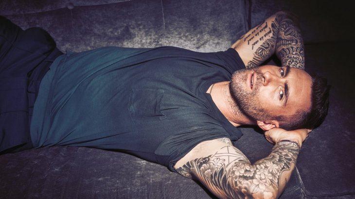 Adam Levine de Maroon 5, hombre con tatuajes, barba y playera gris