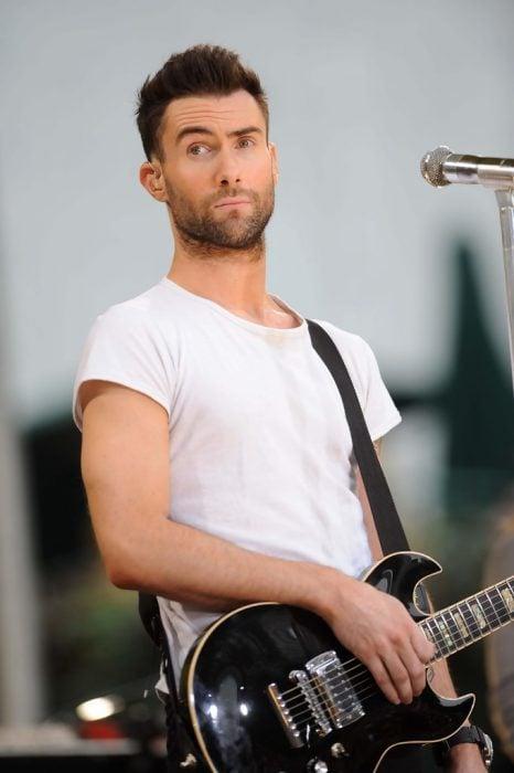 Adam Levine de Maroon 5, hombre con playera blanca tocando la guitarra
