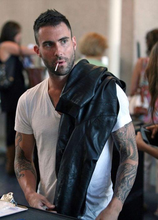 Adam Levine de Maroon 5, hombre con playera blanca y chamarra de cuero