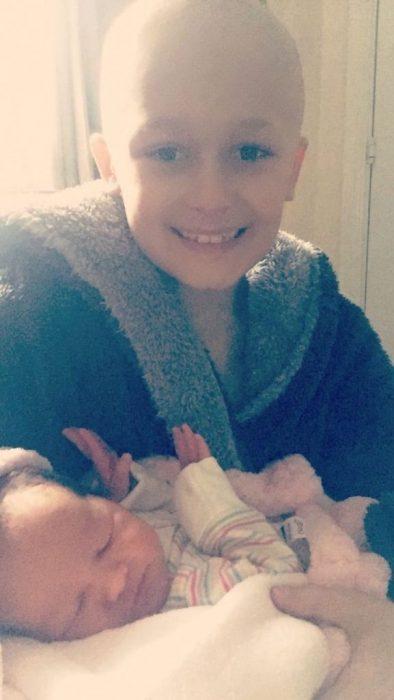 niño sin pelo cargando a niña bebé