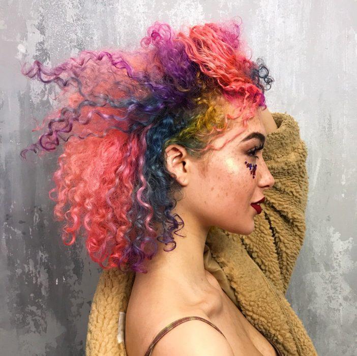 Chica con cabello chino de colores rosa, morado y azul