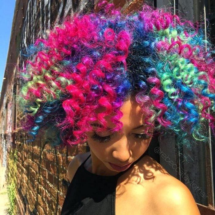 Chica con cabello chino de colores rosa, verde y azul