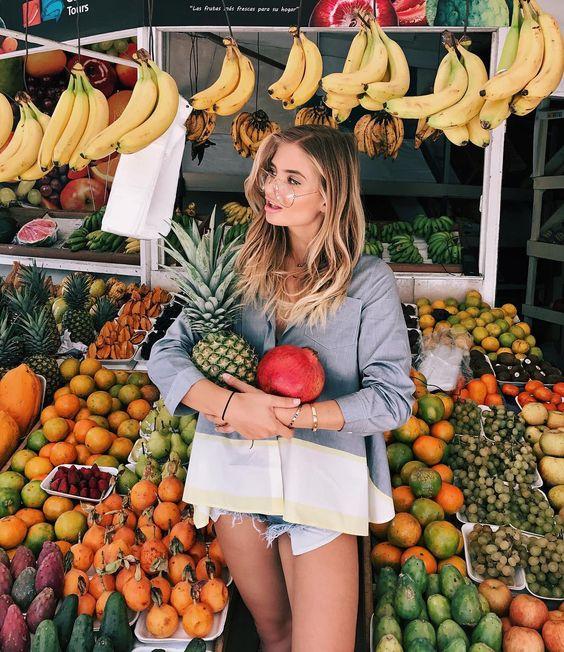 Chica sosteniendo una piña y un mango en un mercado
