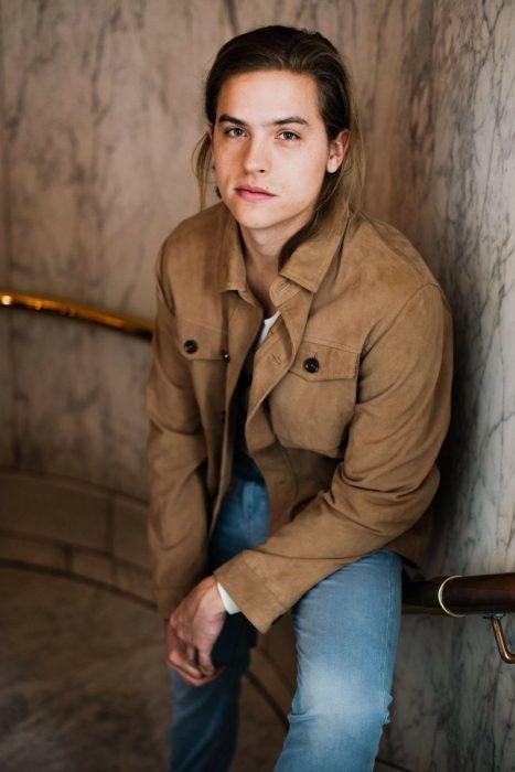 hombre rubio con cabello largo y camisa café