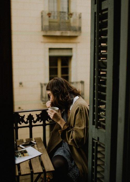 chica tomando café en un balcon