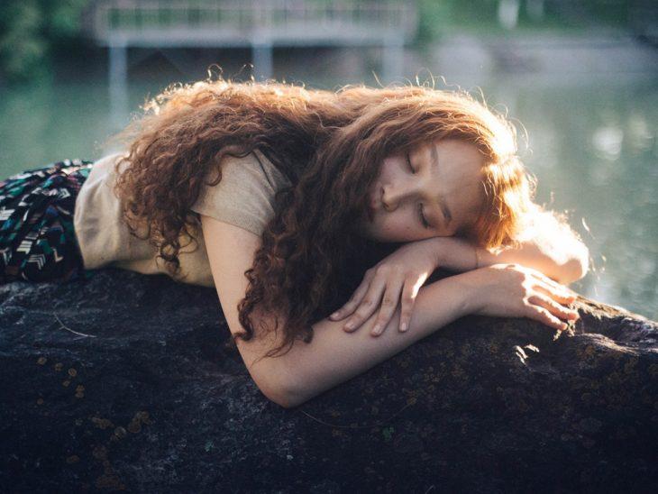 chica recostada en una piedra