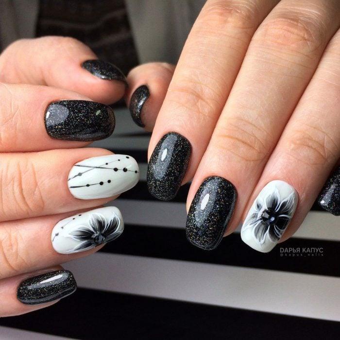 Uñas pintadas de negro y blanco con diseño de flores y puntos